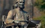 John Carroll Statue holding a laptop