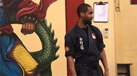 Bryson standing in a dojo studio